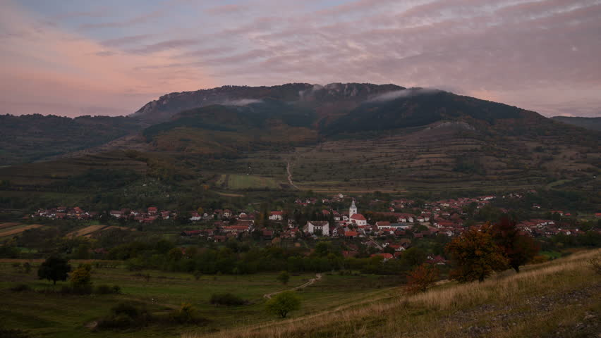 Panorama of Rimetea village at sunrise. Transylvania. View of a remote village in foreground and mountains in background. Dynamic cloudy sky over the Apuseni Mountains, Romania. 4k time lapse.