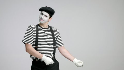 Mime artist pulling an invisible rope isolated on gray backgroun