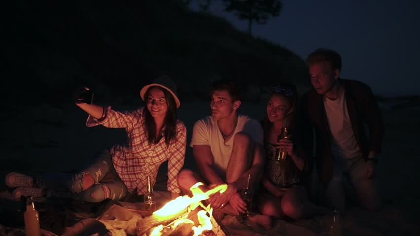 Picnic Of Young People With Bonfire On The Beach In The Evening. Cheerful  Friends Taking