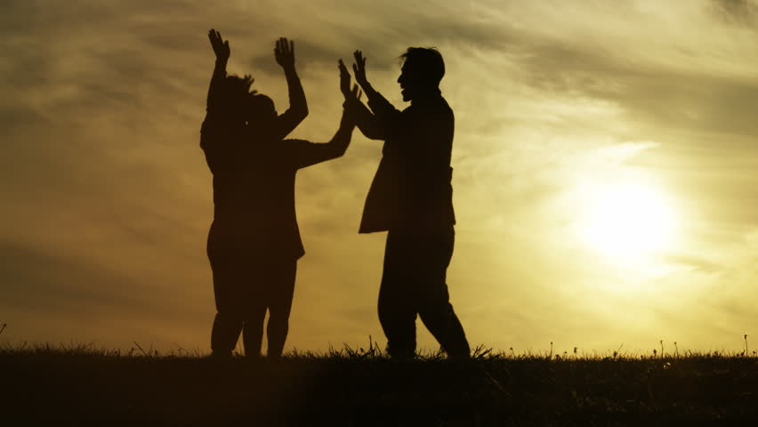Three people talking at sunset high five each other, in slow motion | Shutterstock HD Video #28114765