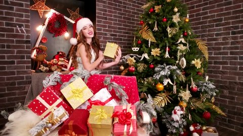 Sexy Elf adds New Year's gifts, girl in Santa's hat is preparing holiday boxes for Christmas, Many bright gifts and interesting toys on Christmas days, Beautiful girl and Happy Winter Holidays