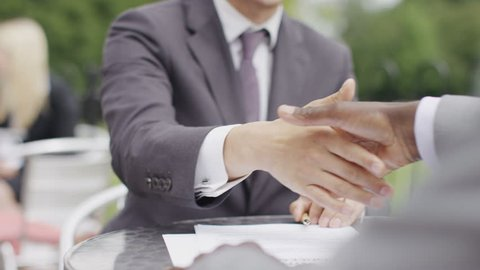 Young asian man in a suit signs a sheet and shakes hands during an outdoor meeting