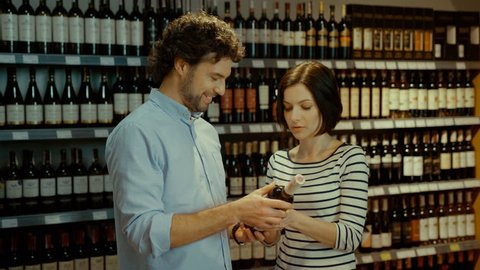 Young attractive couple trying to choose good bottle of wine in the supermarket on background with wine bottle.