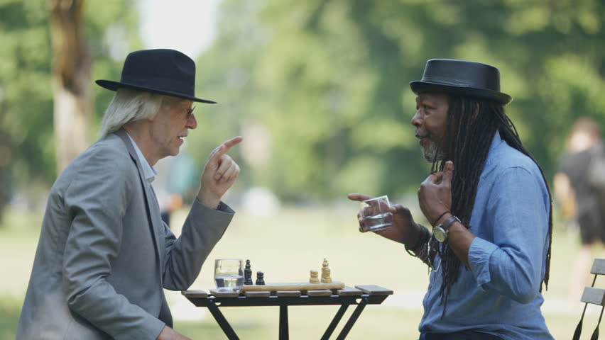 Two old retired friends have a chat before a game of chess in the park