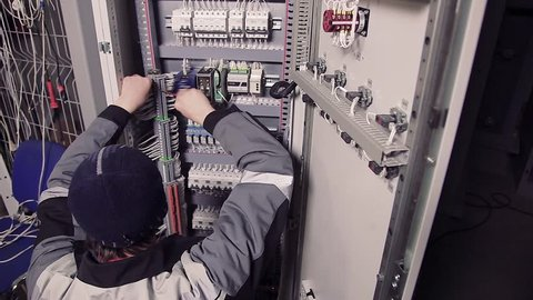 Man working with wires in electric meter.