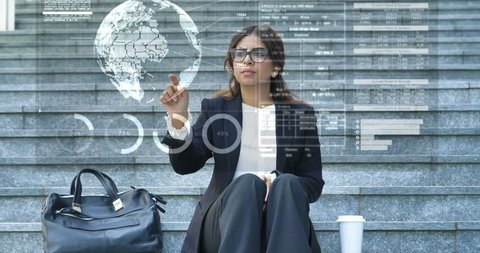 Futuristic portrait of a business woman, student in a suit, glasses, uses a holographic hologram of the world ball, sits on the stairs. Concept: future, fast Internet, network, communication, contacts