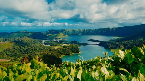 Establishing shot of the famous Lagoa das Sete Cidades lake seen behind green vegetation, in Sao Miguel, The Azores, Portugal