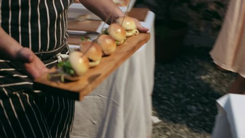 Waiter brings tray with mini burgers made of organic ingridients to table of authentic hipster bar and hungry party people immediately take them away, little canape are perfect snacks
