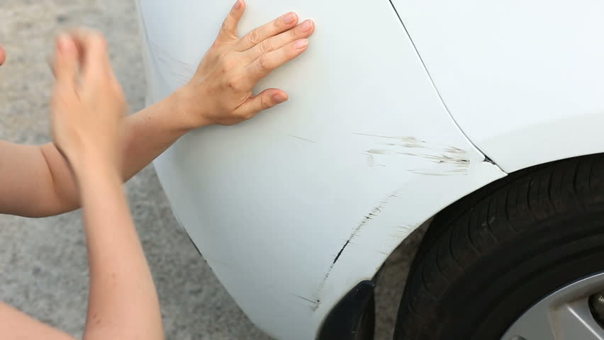 looking at a damaged vehicle. Woman blonde inspects car damage after an accident