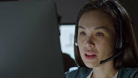 PAN of serious female Asian helpline operator in headset with microphone talking with person on voice call