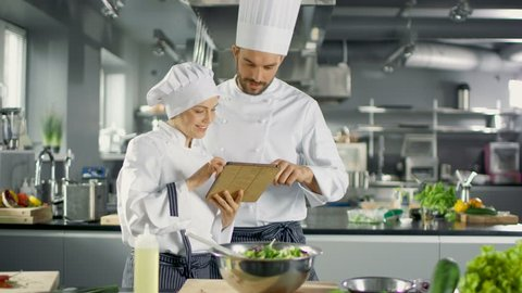 Male and Female Famous Chefs Discuss Their Video Blog while Using Tablet Computer. They Work on a Big Restaurant Stainless Steel Professional Kitchen.