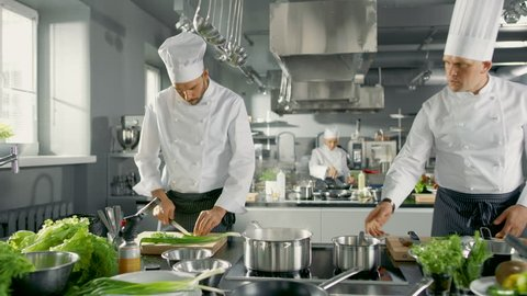 Two Famous Chefs Work as a Team in a Big Restaurant Kitchen. Vegetables and Ingredients are Everywhrere, Kitchen Looks Modern with Lots of Stainless Steel.   Shot on RED EPIC-W 8K Helium Cinema Camera