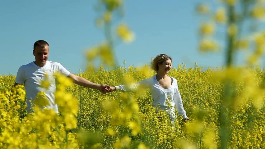 Young couple runs across the field of rape