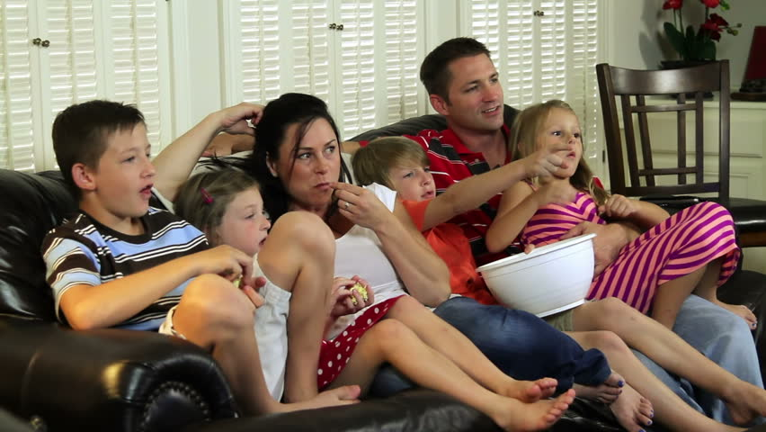 Mom and dad and four children enjoy watching TV together.