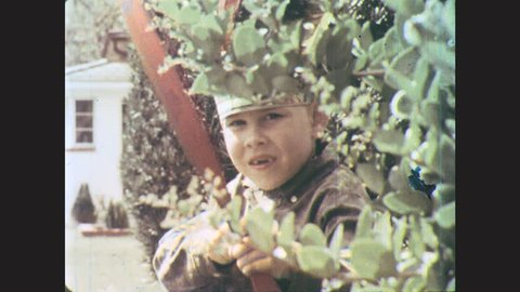 1960s: UNITED STATES: boy dressed as Indian hides in garden. Boy loads catapult. Boy loads arrow on bow. Boy fires catapult