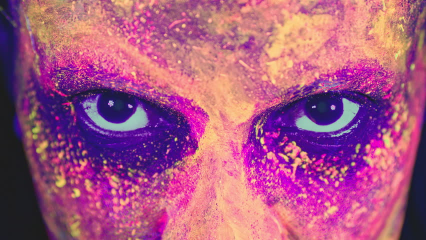 Mysterious woman with UV painting looks into the camera