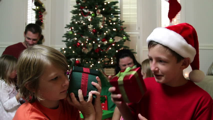 Two young boys in a family Christmas scene shake their presents as if trying to determine the contents.