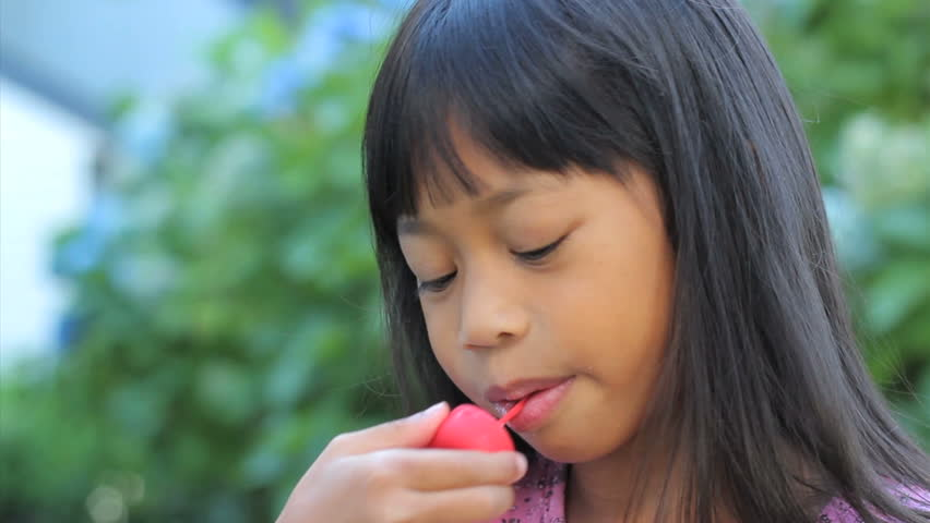 A Cute Little 6 Year Old Asian Girl Enjoys Licking Her Popsicle On A Hot Summers Day -7003