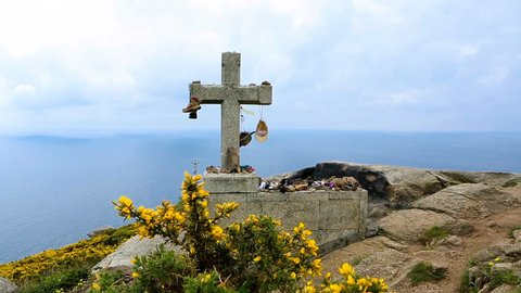 Cross stone rock Cape Finisterre (Cabo Finisterre, Spain) final destination for pilgrims Camino de Santiago. Traditionally wayfarers leave they clothes and shoes. video footage
