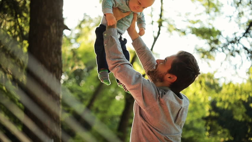 Young dad is throwing up his cute little baby at green park in the rays of sun | Shutterstock HD Video #28351717