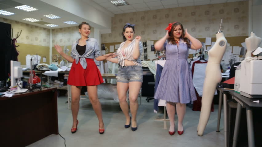 Beautiful curvy girls imagined as pin-up seamstresses at a clothing workshop