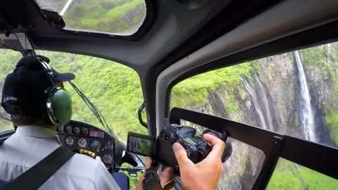 EPERON, REUNION ISLAND, FRANCE - NOVEMBER 7, 2015: Flight over amazing waterfals in The Trou de Fer - Iron Hole canyon in Cirque Salazie. Photographer taking aerial photos from helicopter.