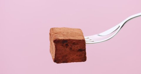 stop motion of someone eats a truffle on fork. invisible bites