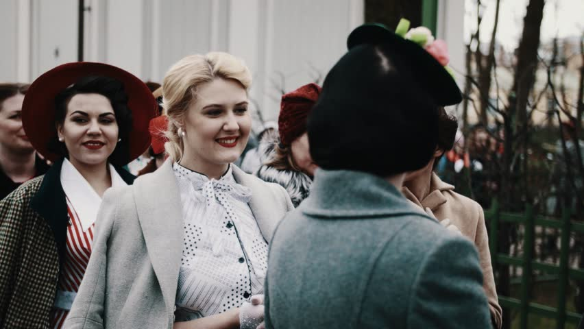 SAINT PETERSBURG, RUSSIA - MAY 9, 2017: Beautiful women group in retro dresses with red lipstick smiling posing in city park cold autumn cloudy day | Shutterstock HD Video #28423909