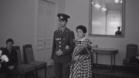 SAINT PETERSBURG, RUSSIA, 1983: Old vintage black and white film military man holds cap, kisses pregnant wife at wedding court