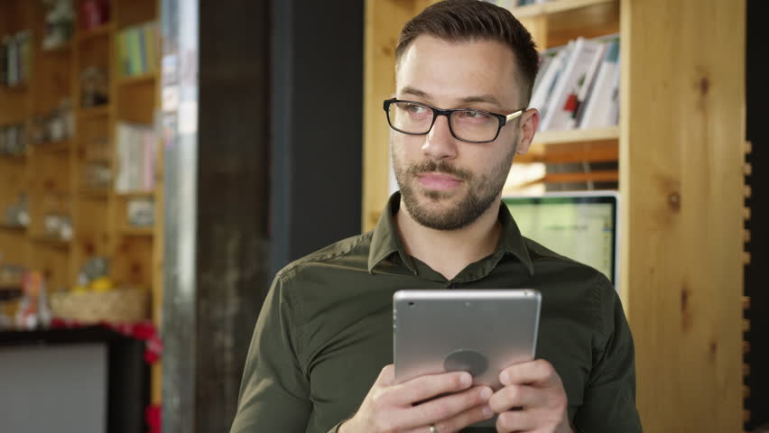 Handsome Professional Young Entrepreneur Testing An Online Application On An iPad Messaging Playing Texting Smiling Happy Relaxed Technology Connection Concept Slow Motion Shot On Red Epic 8K