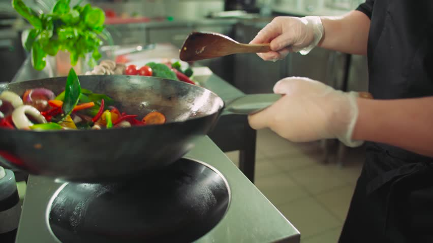 close-up chef actively working in the kitchen of an Asian restaurant mixed colorful vegetables are roasted in a wok in slow motion