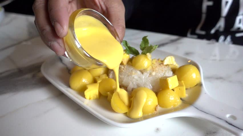 Pouring homemade mango sauce into mango sticky rice.