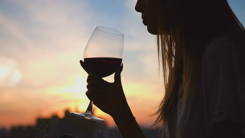 Young woman drinking red wine from a glass and watching on sunset through the window. Close up.