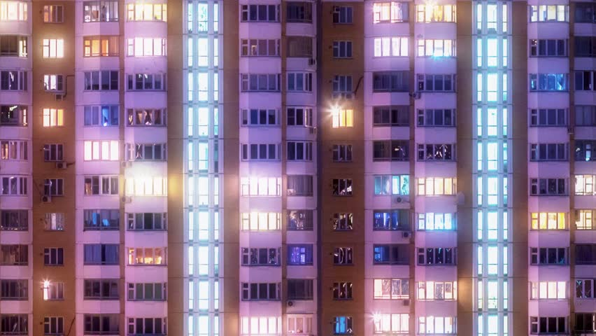 Windows of city building illuminated at night. Timelapse.