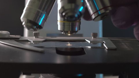 Scientist tune sample position on a microscope by moving it in 3d space and then changes objective lens to get better magnification