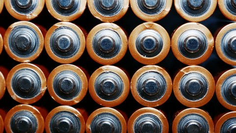 Energy abstract Background of Batteries. The top view of the AA-Size Battery. Used Alkaline Batteries . Close Up