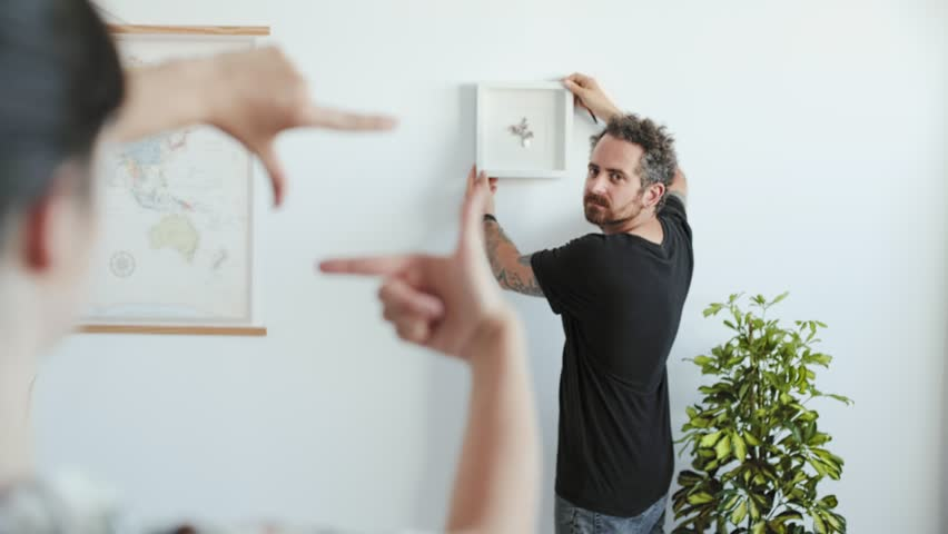 Young happy millennial couple students move into their first new owners home. Simple white background of urban apartment, they frame and decide on decoration on walls, painting and map | Shutterstock HD Video #28567267