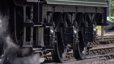 Black and white shot of steam train wheels moving on track
