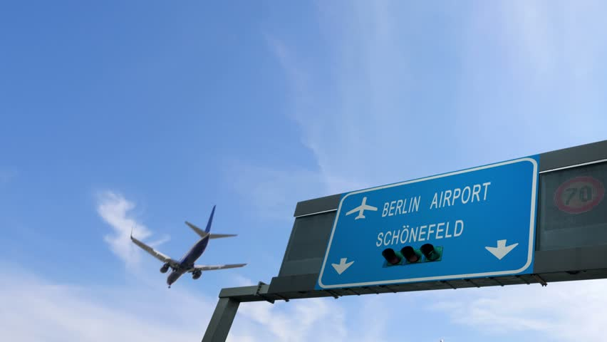 airplane flying above berlin airport signboard