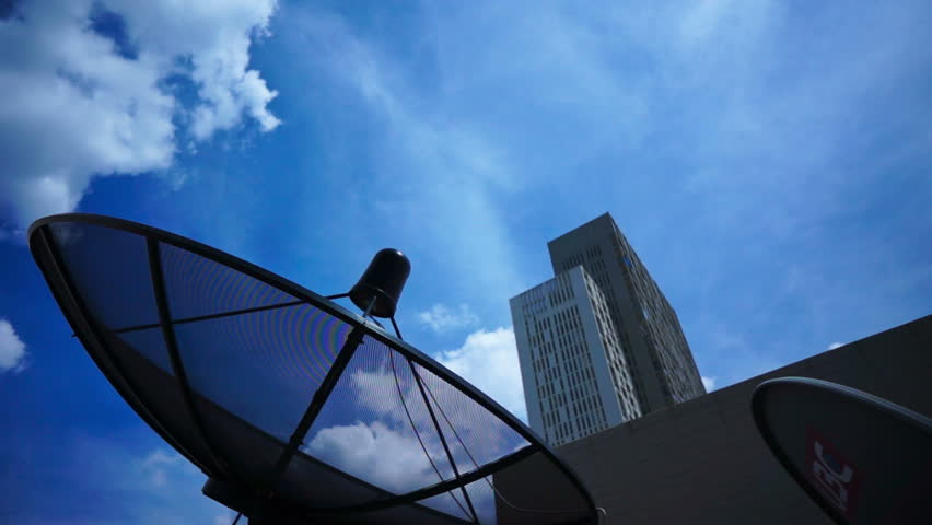 Black antenna communication satellite dish over sky in cityscape - time-lapse