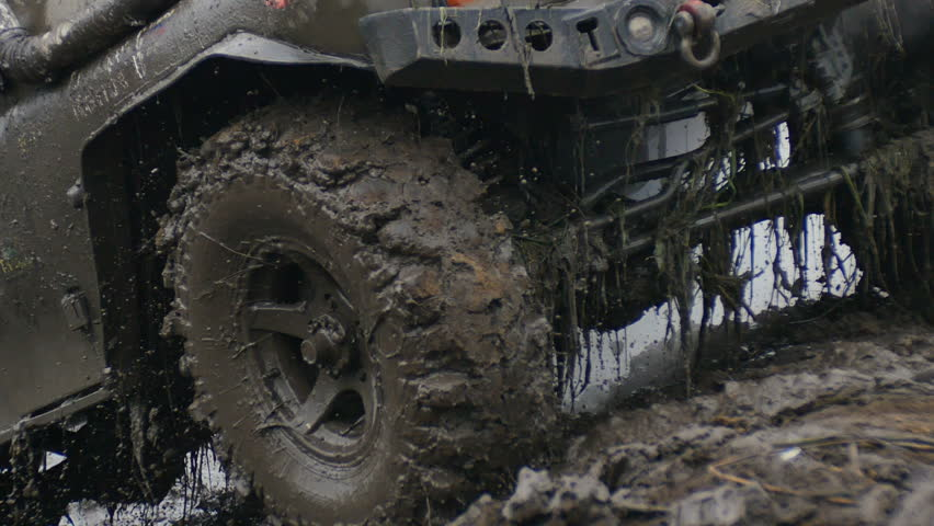 Close up of wheel in the Mud. Off-road car wheel slips in the mud, but moves slowly.