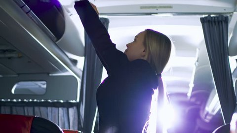 Airplane Stewardess/Flight Attendant Closes Baggage Compartments. Plane is Ready to Take off. Shot on RED EPIC-W 8K Helium Cinema Camera.
