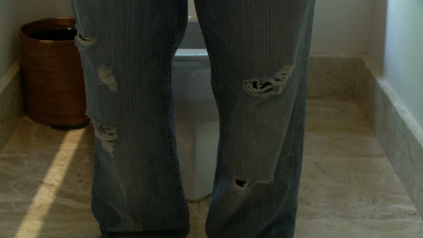 Male pulling jeans down and sitting on the toilet tapping his foot