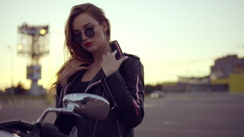 Portrait of a female biker in leather jacket and shorts sitting on her bike and holding a handlebar. Close up of young sexy curly woman in sunglasses on the chopper
