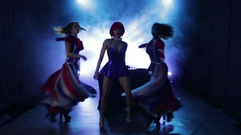 Trio of sexy girls erotic dance in smoky studio background