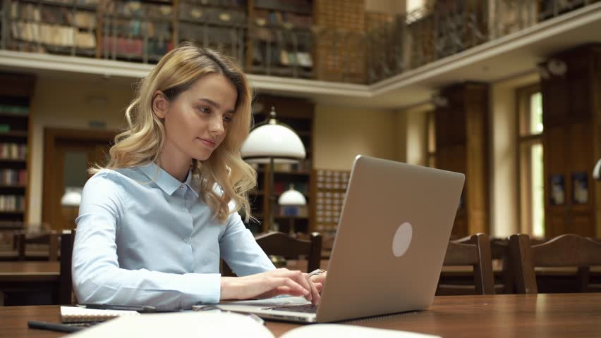 Student works with books and laptop in the library