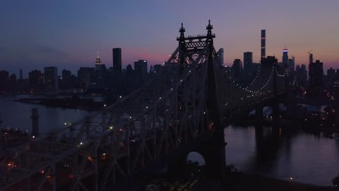 dusk flying alongside Queensboro Bridge towards Manhattan
