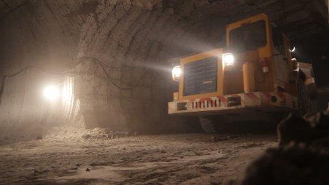 KAZAN, TATARSTAN/RUSSIA - MAY 24 2013: Yellow large modern powerful dumper truck drives past camera along dark wide underground tunnel on May 24 in KAZAN