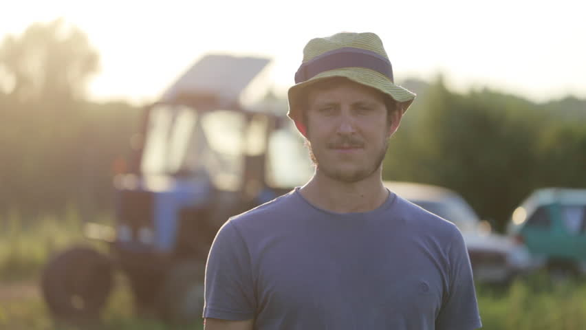 Portrait of young farmer in hat standing at field of organic farm with the tractor on the background. Man looking at camera and smiling in beautiful sunset light. | Shutterstock HD Video #28703551