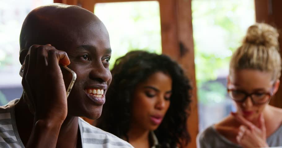 Happy man talking on mobile phone in café | Shutterstock HD Video #28704277